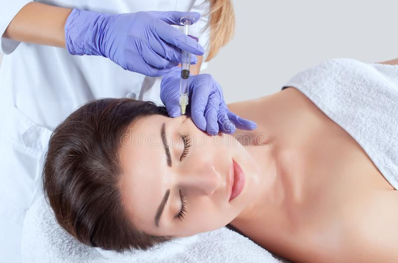 Le cosmetologist de docteur fait la procédure faciale rajeunissante d'injections pour serrer et lisser des rides photographie stock
