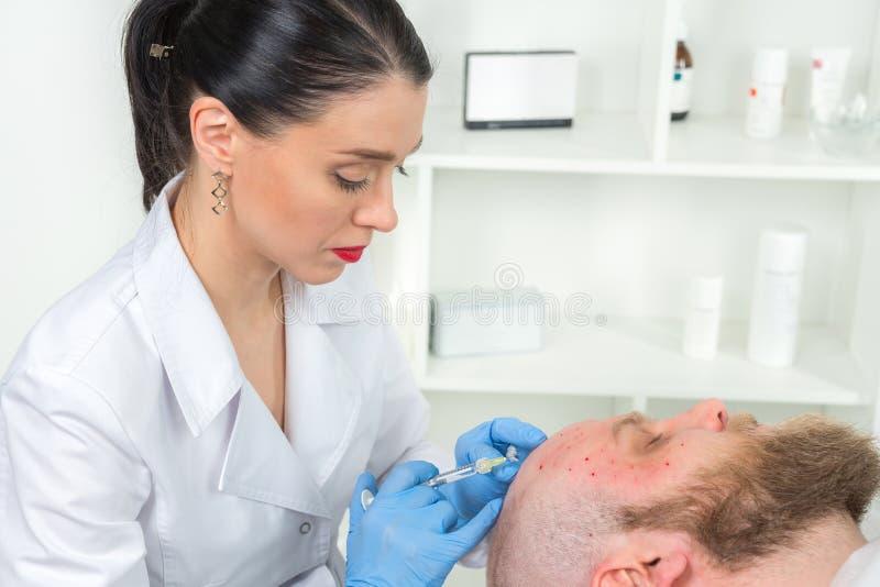 Le cosmetologist de docteur fait la procédure faciale rajeunissante d'injections pour serrer et lisser des rides sur la peau de v photographie stock libre de droits