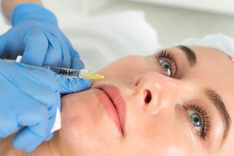 Le cosmetologist de docteur fait la procédure faciale rajeunissante d'injections pour serrer et lisser des rides sur la peau de v image libre de droits
