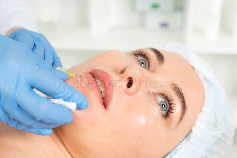 Le cosmetologist de docteur fait la procédure faciale rajeunissante d'injections pour serrer et lisser des rides sur la peau de v image stock
