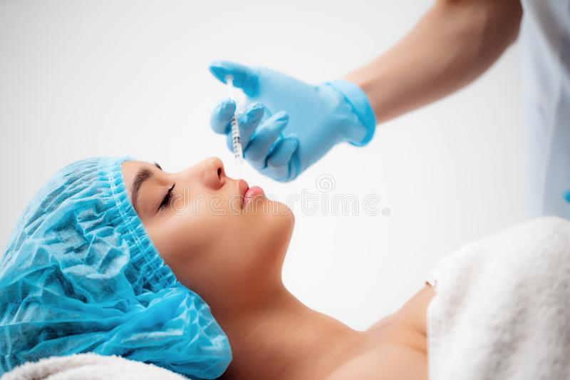Le cosmetologist de docteur fait la procédure faciale rajeunissante d'injections pour serrer et lisser des rides sur image libre de droits