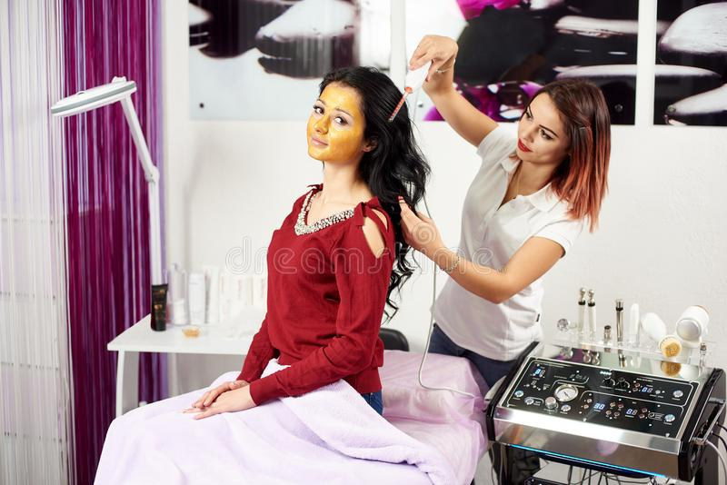 Le Cosmetologist donne le traitement de cheveux à un client de brune avec un masque d'or sur son visage dans un salon de beauté m photographie stock