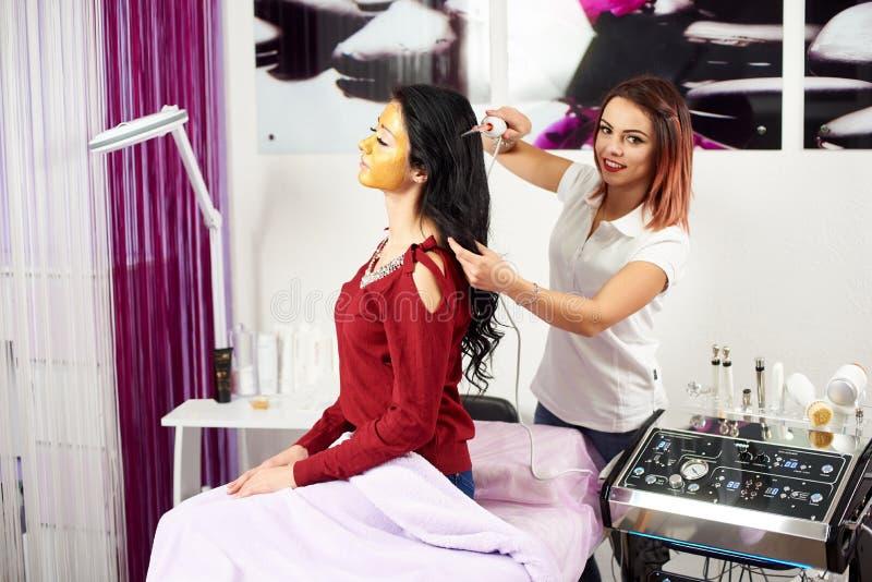 Le Cosmetologist est souriant et regardant dans l'appareil-photo tout en donnant le traitement de cheveux à la femme de brune dan images stock