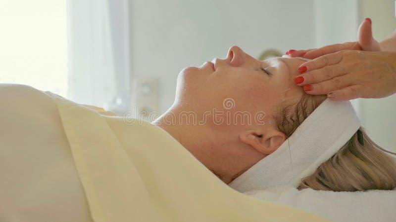 Le Cosmetologist est visage du ` s de femme de nettoyage par l'éponge de coton au salon de station thermale photos libres de droits