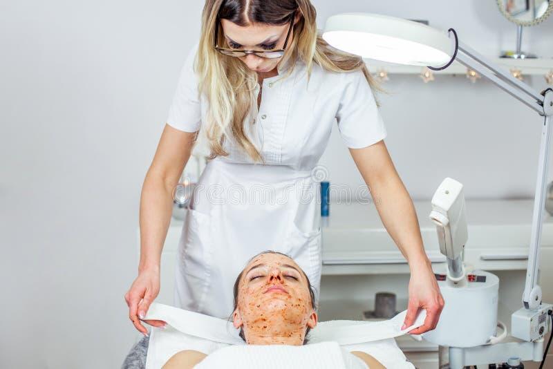 Le Cosmetologist fait le masque d'épluchage de visage, traitement de beauté de station thermale pour la jeune fille Modèle, plan  photo stock