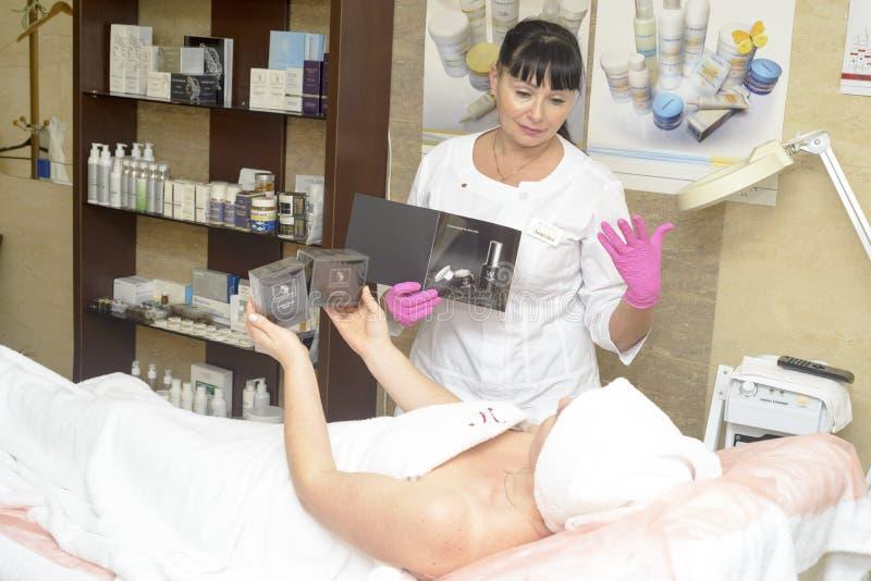 Le cosmetologist offre les cosmétiques de client, Ukraine, village de Polyana, décembre 2018 images stock