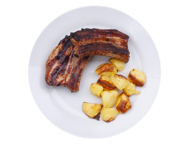 Le costole appiccicose arrostite col barbecue e le braciole di maiale dalla griglia con il forno hanno cotto le patate su un piat fotografia stock libera da diritti