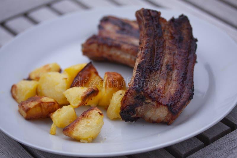 Le costole appiccicose arrostite col barbecue e le braciole di maiale dalla griglia con il forno hanno cotto le patate su un piat fotografie stock