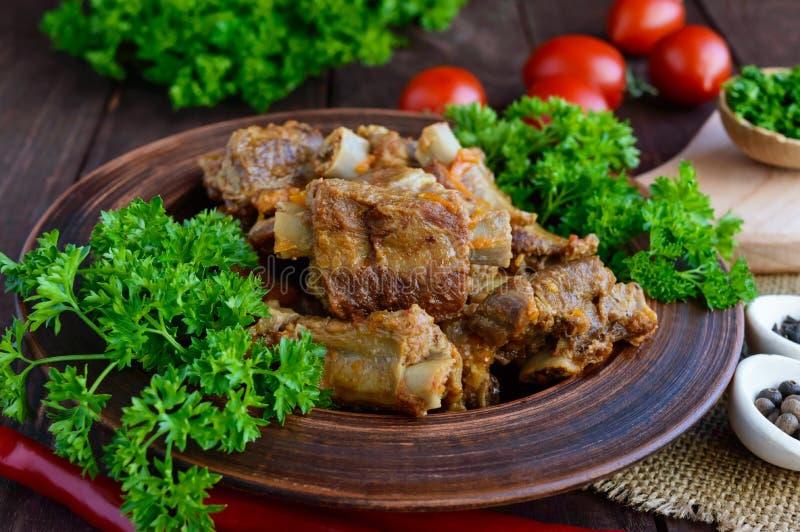Le costole di carne di maiale hanno cotto a vapore con le carote, prezzemolo decorato fotografia stock