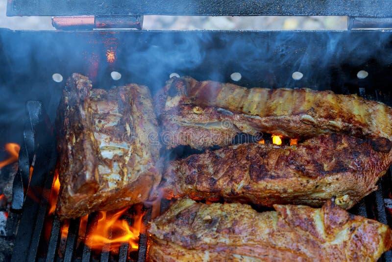 le costole di carne di maiale del bbq che cucinano sulla griglia ardente hanno sparato con il fuoco selettivo fotografia stock
