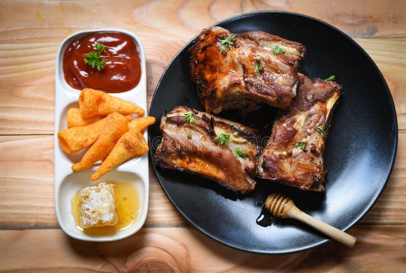 Le costole di carne di maiale del Bbq grigliate con la salsa del miele e le spezie dolci delle erbe sono servito sulla tavola - c fotografia stock libera da diritti