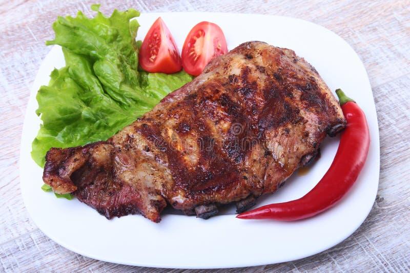 Le costole di carne di maiale sul barbecue e sul peperoncino con il pomodoro, lattuga va sul piatto bianco immagine stock