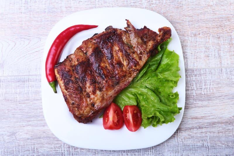Le costole di carne di maiale sul barbecue e sul peperoncino con il pomodoro, lattuga va sul piatto bianco fotografia stock libera da diritti