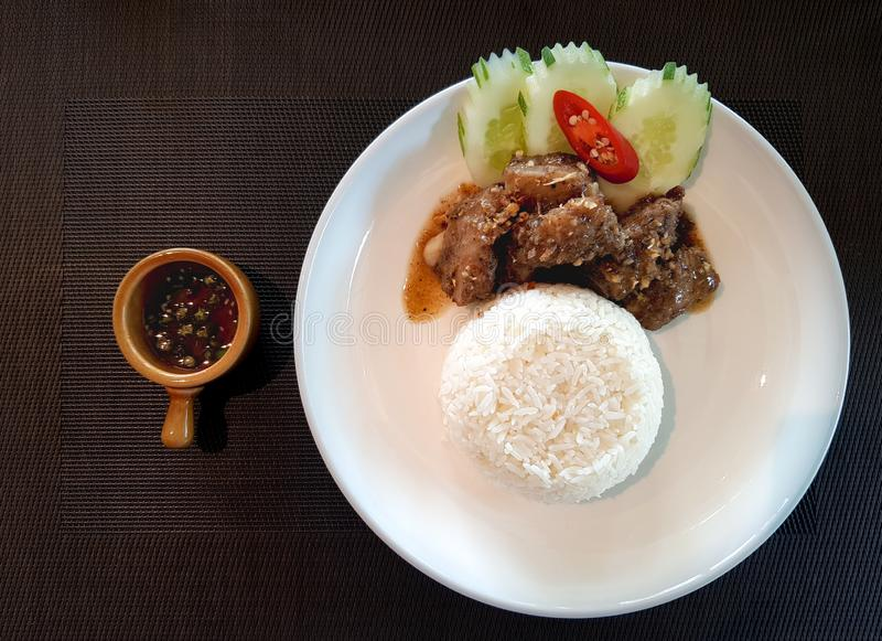 Le costole di carne di maiale tagliate hanno fritto con il sugo dell'aglio con riso bianco fotografie stock