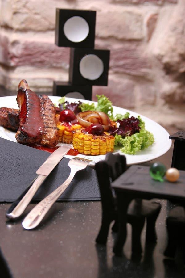 Le costole grigliate dell'agnello sono servito con cereale arrostito, il salat, salsa del bbq, su un piatto bianco immagine stock libera da diritti