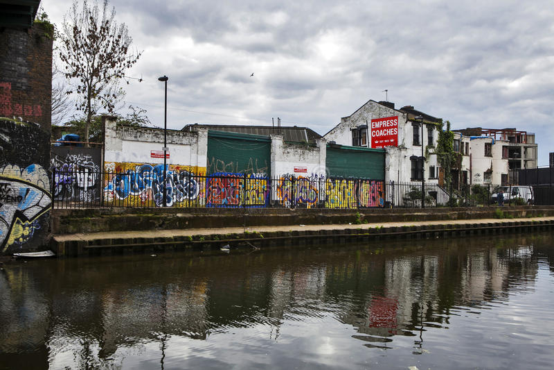 Le costruzioni abbandonate dipinte dai graffiti, lungo Regent Canal, vicino alla strada di Broadway Area urbana immagine stock