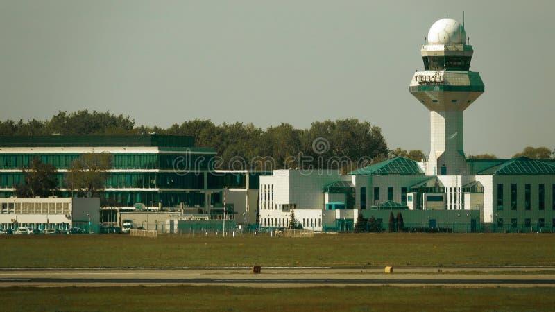 Le costruzioni e la torre di controllo dell'aeroporto oltre la pista riscaldano la foschia Colpo del teleobiettivo fotografie stock