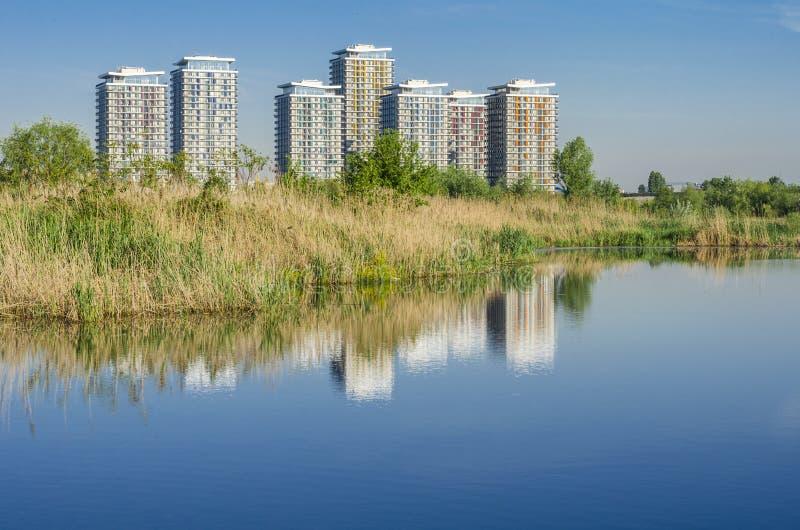 Le costruzioni riflettono in acqua immagini stock