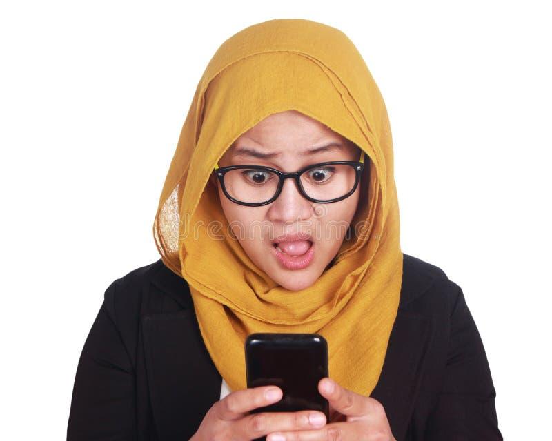 Le costume de port de jeune femme d'affaires asiatique a choqué l'expression, regardant son téléphone images libres de droits