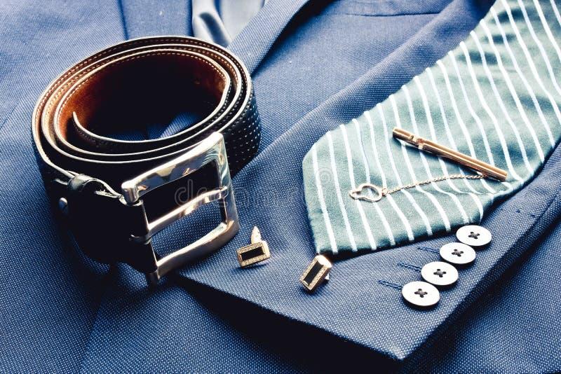Le costume des hommes classiques de mode avec la ceinture en cuir noire, le lien bleu rayé, les ufflinks d'or et l'agrafe de lien image libre de droits