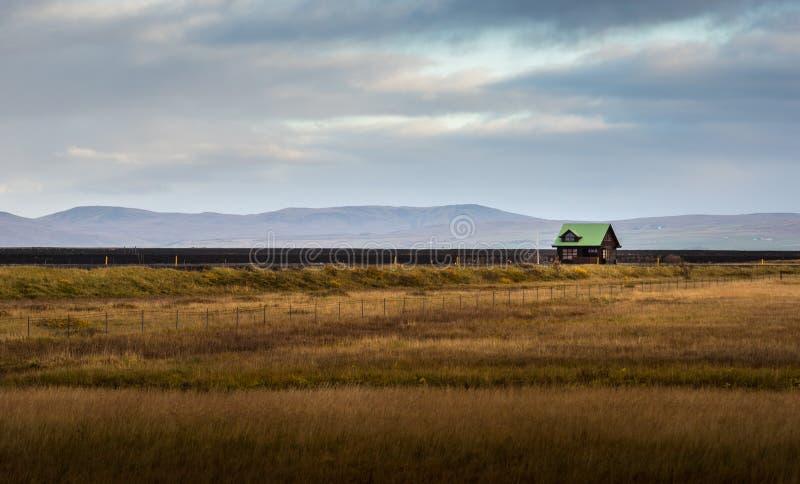 Le cottage vert isolé de toit dans l'herbe jaune a classé avec le fond de gamme de montagne photos stock