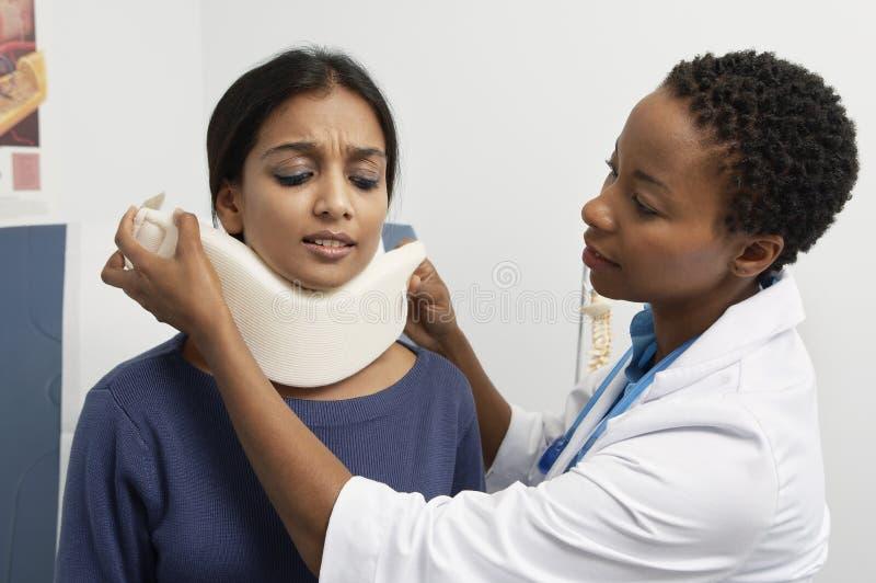 Le cou du patient féminin de docteur Putting Brace On photos libres de droits