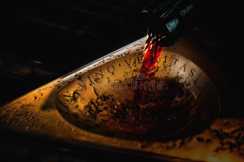 Le cou foncé de bouteille avec du vin courant rouge à un d'or antique plat image stock