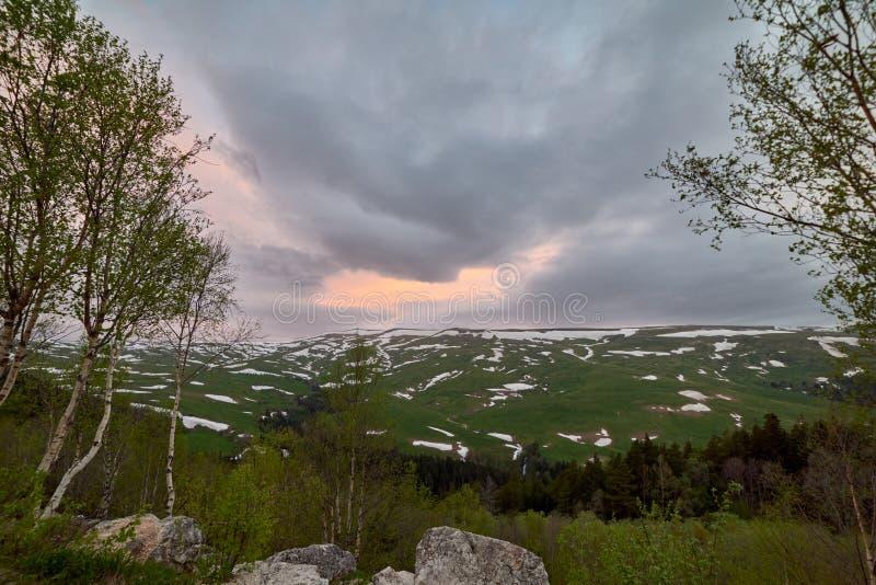 Le coucher de soleil au-dessus du plateau de vert de montagne avec des champs de neige image stock