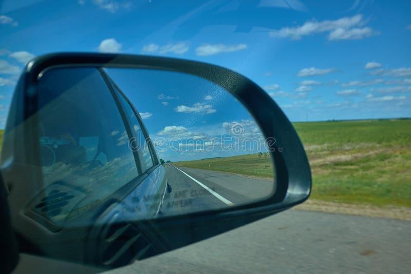 Le coucher du soleil bleu de paysage de ciel nuageux se reflètent dans le miroir de la voiture photos stock