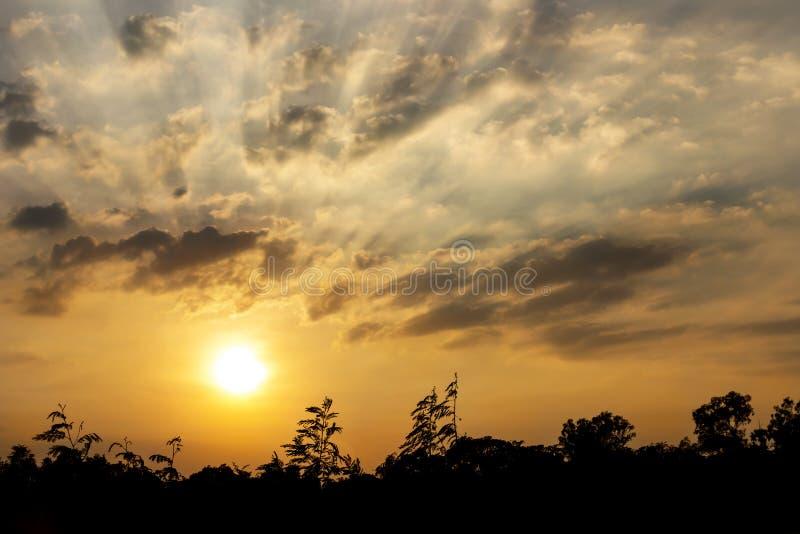 Le coucher du soleil dans le temps crépusculaire avec les nuages et le soleil brille par r images libres de droits