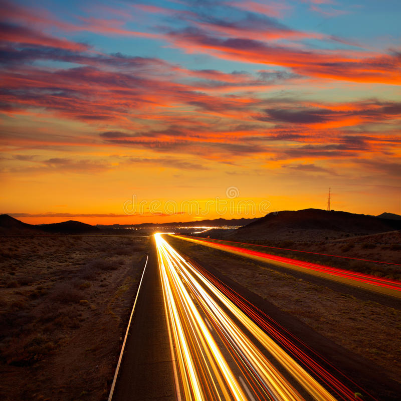 Le coucher du soleil de l'Arizona à l'autoroute 40 avec la lumière de voitures trace image stock