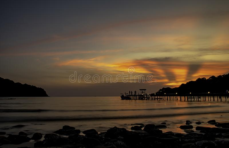 Le coucher du soleil derrière l'île en mer et l'ombre des touristes sur le pont en bois chez Koh Kood, Trat en Thaïlande photographie stock