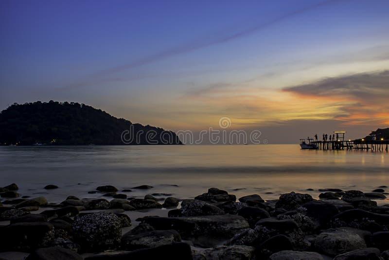 Le coucher du soleil derrière l'île en mer et l'ombre des touristes sur le pont en bois chez Koh Kood, Trat en Thaïlande image libre de droits