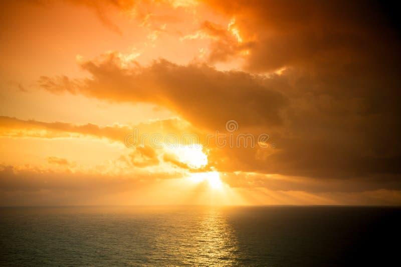 Le coucher du soleil dramatique rayonne par un ciel foncé nuageux au-dessus de l'océan T image libre de droits