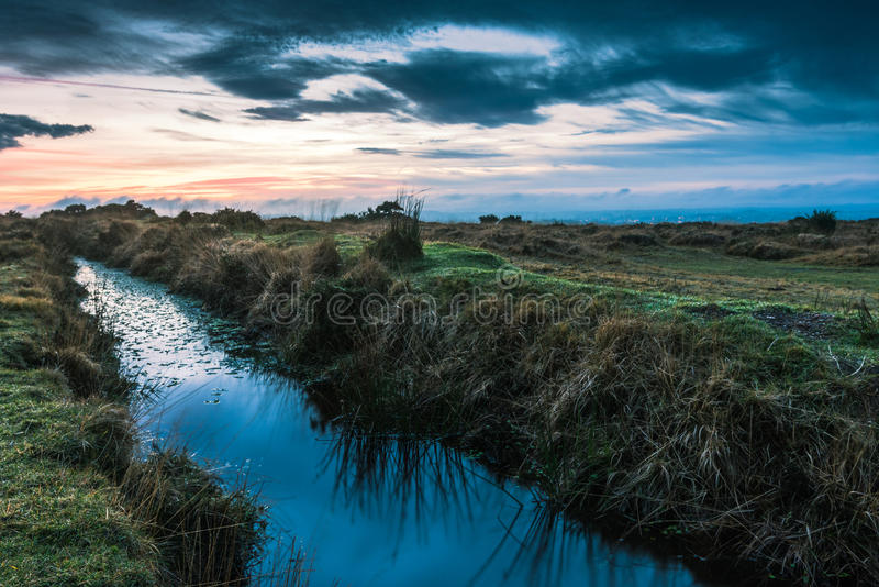 Le coucher du soleil dramatique se reflètent dans l'eau sauvage de crique image stock