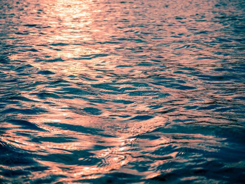 Le coucher du soleil illumine les vagues bleues dans le lac cottage photographie stock