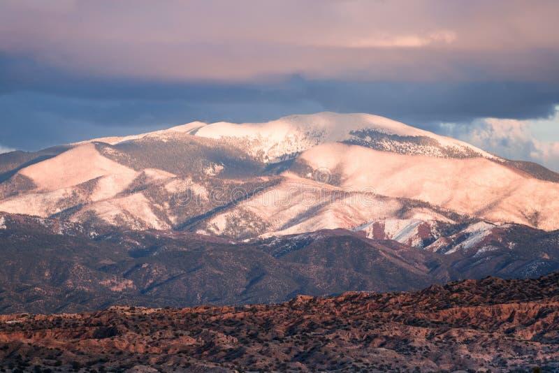 Le coucher du soleil illumine Sangre de Cristo couronné de neige Mountains et nuages et bad-lands colorés près de Santa Fe, Nouve photos libres de droits