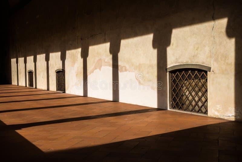 Le coucher du soleil moule les ombres de la colonnade sur la galerie avec des fenêtres saisies avec des barres d'acier et Flor de photos stock