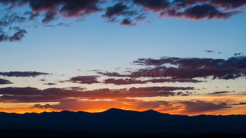 Le coucher du soleil silhouette une gamme de montagne et illumine un ciel égalisant dramatique avec les nuages pourpres et roses photo libre de droits