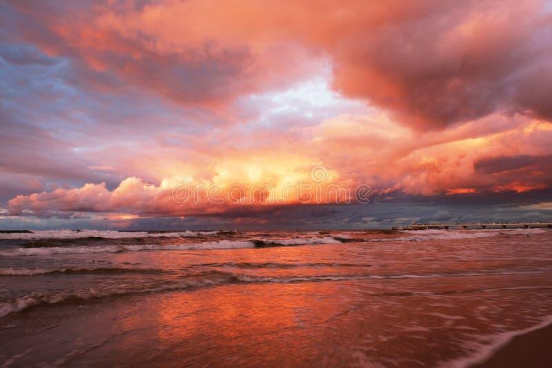 Le coucher du soleil sur la mer, a admirablement accentué les nuages, vagues sur la côte baltique photos stock