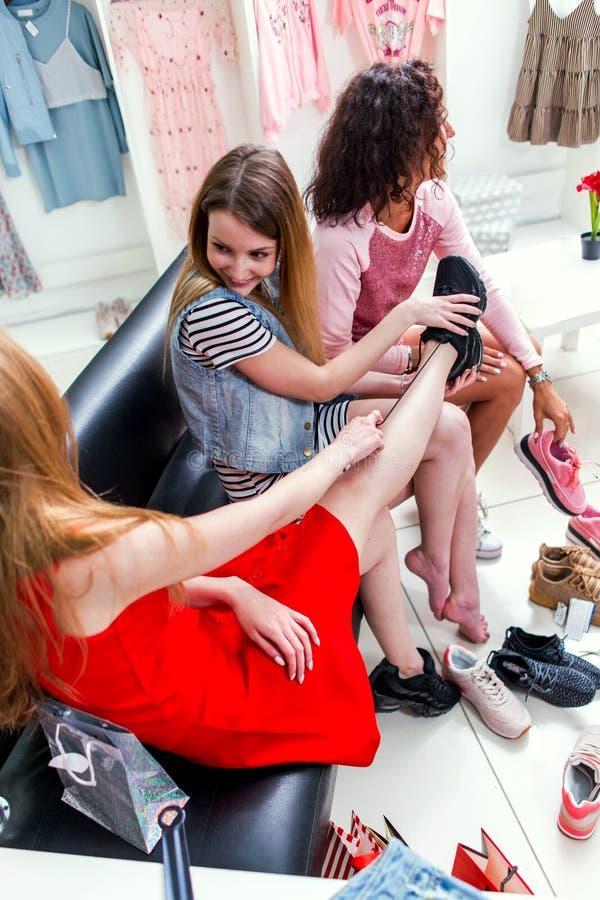 Le coup courbe des amies de sourire choisissant la mise sur des sports chausse se reposer sur le banc causant et riant tandis que photographie stock libre de droits