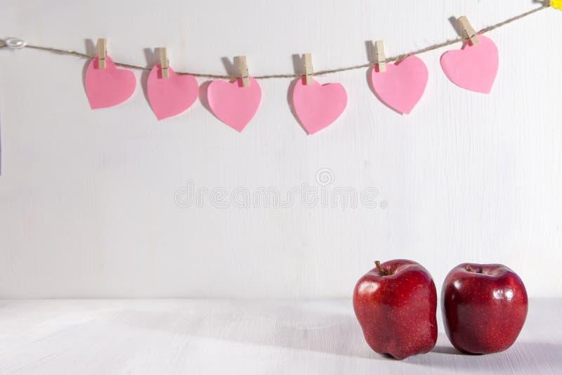 Le coup de papier de coeurs sur le mur Deux pommes rouges sont sur la table, carte de Valentine photos stock