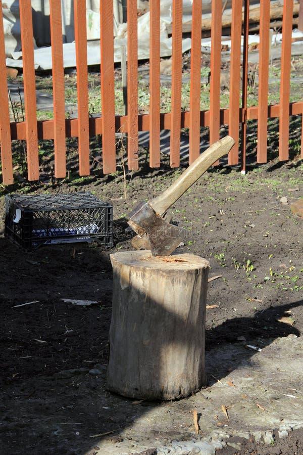 Le couperet en bois colle dans le chanvre en bois Hache et poignée de hache Déboisement par une hache pointue Hache pour couper l images stock
