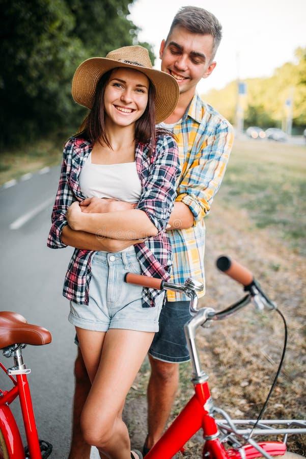 Le couple étreint en parc, vélo de vintage, date romantique photographie stock libre de droits
