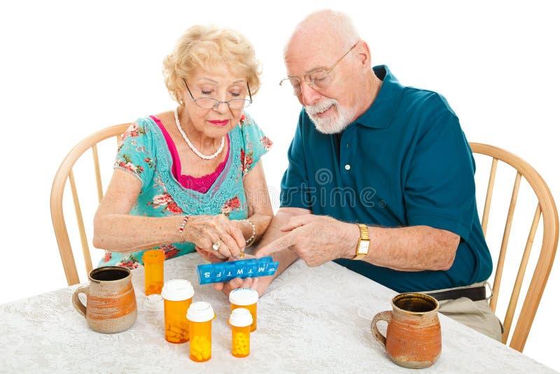 Le couple aîné trie des médicaments image stock