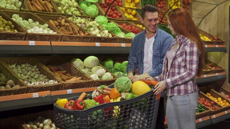 Le couple achète des légumes au mail image libre de droits