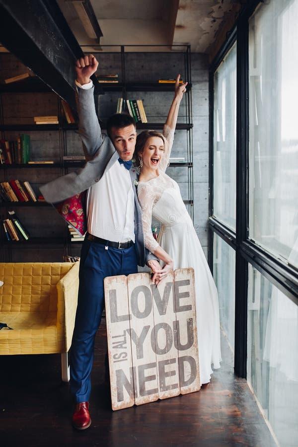 Le couple affectueux embrassant tenant l'enseigne toute que vous avez besoin est amour image stock