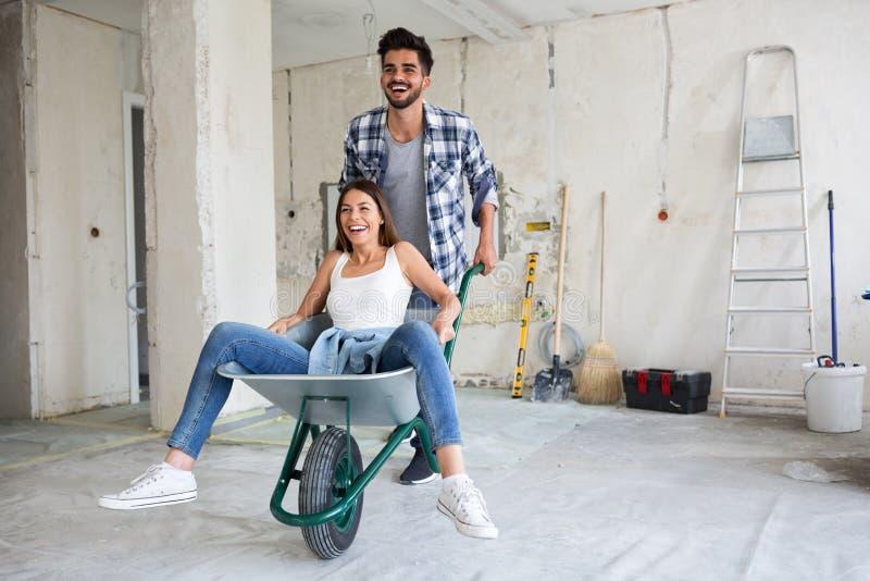 Le couple affectueux a l'amusement tandis qu'ils rénovent la maison photographie stock libre de droits