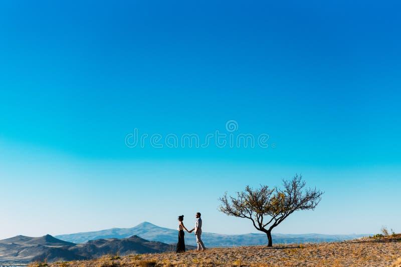 Le couple aimant rencontre le coucher du soleil dans les montagnes photos stock