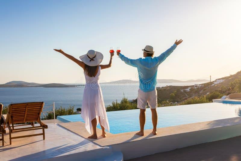 Le couple apprécie le coucher du soleil à la mer Méditerranée par la piscine photos libres de droits